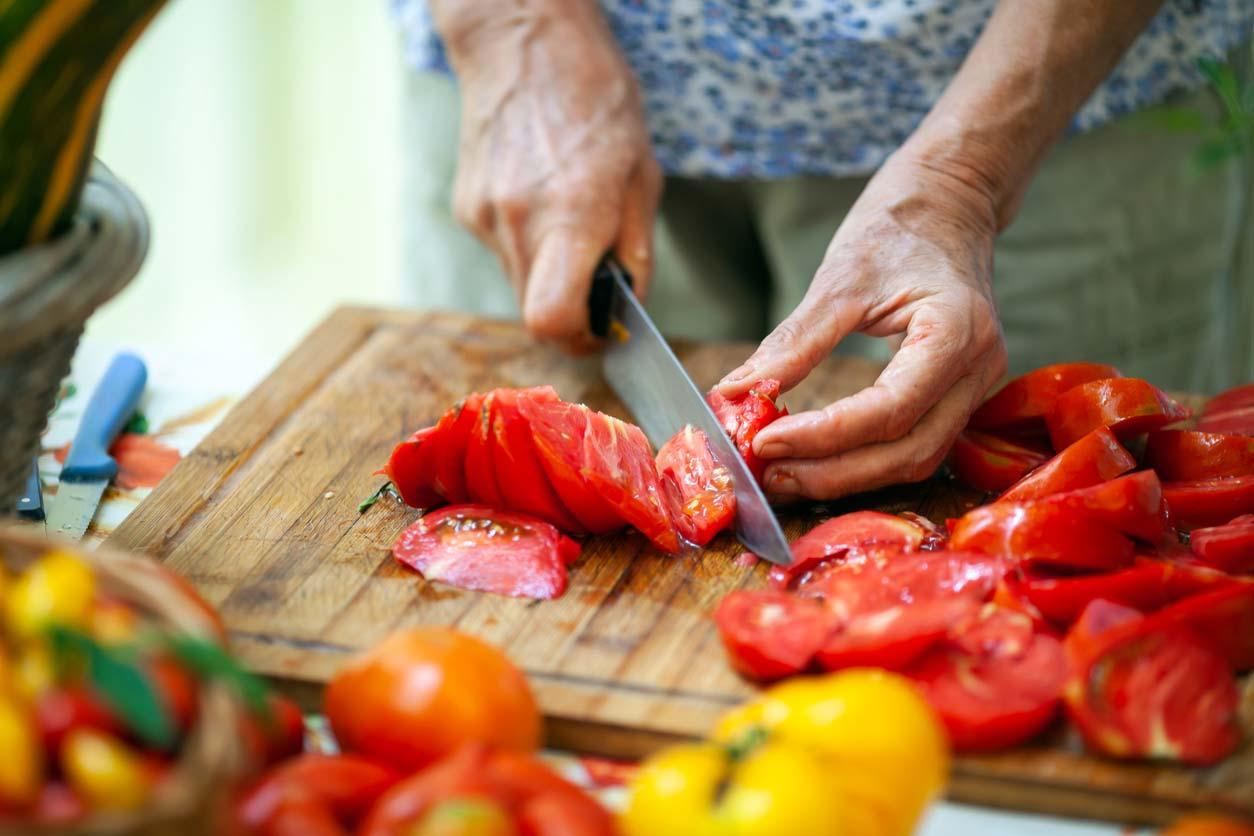 closeup elderly woman slicing tomatoes