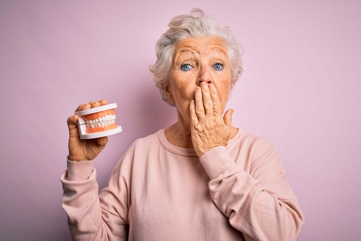 senior woman holding denture teeth