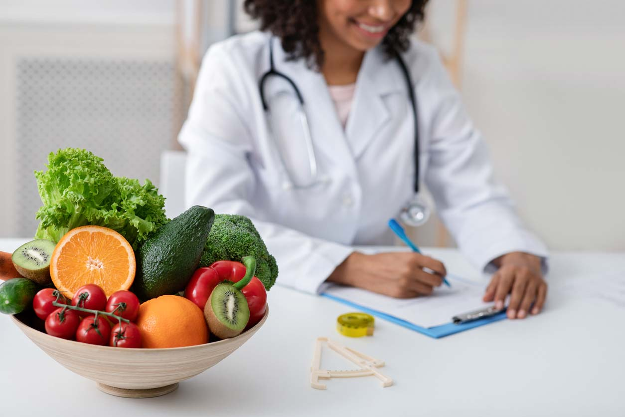 doctor writing out a produce prescription with bowl of fresh fruits and vegetables on desk
