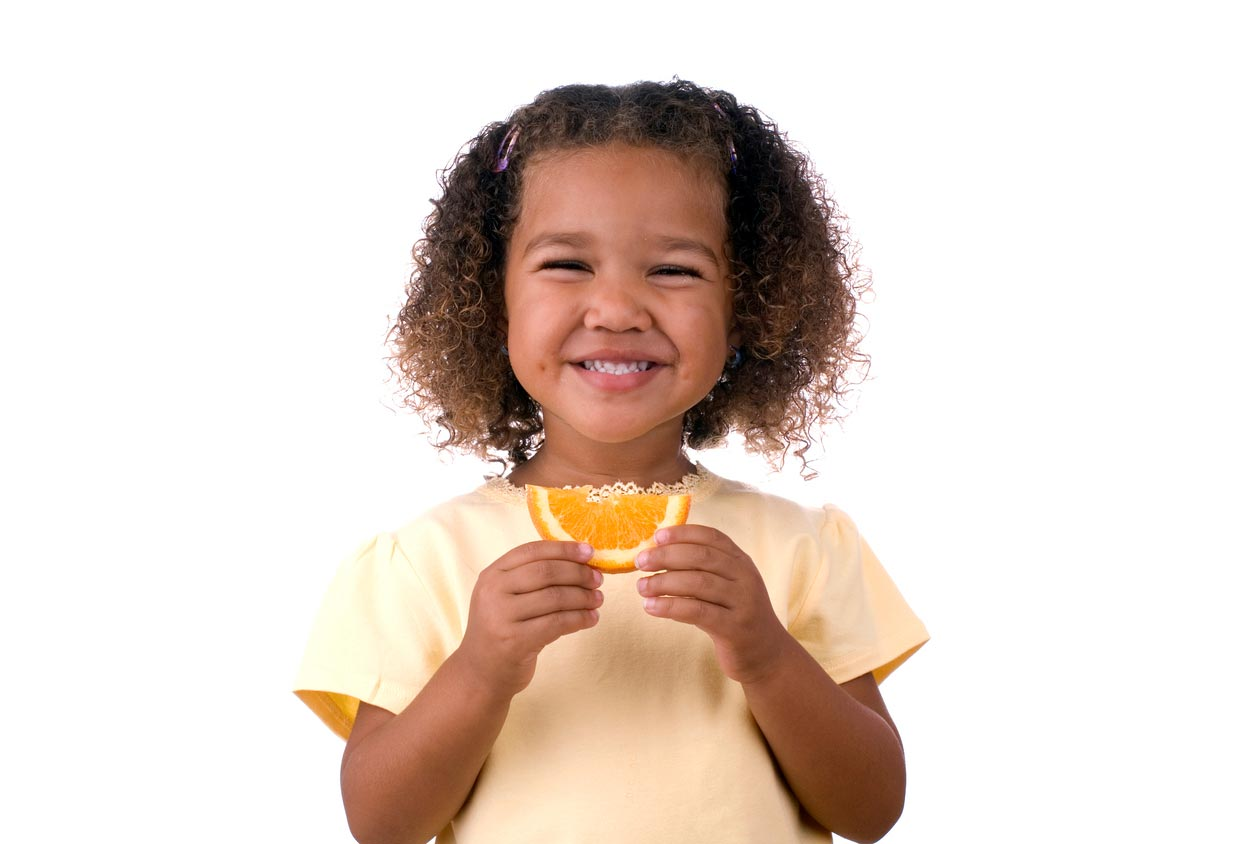 little girl holding an orange slice