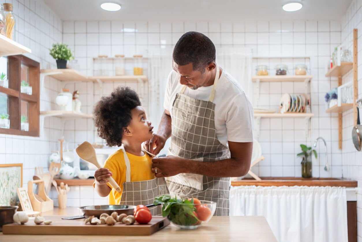 happy African father and son dress up together before cooking in the white kitchen