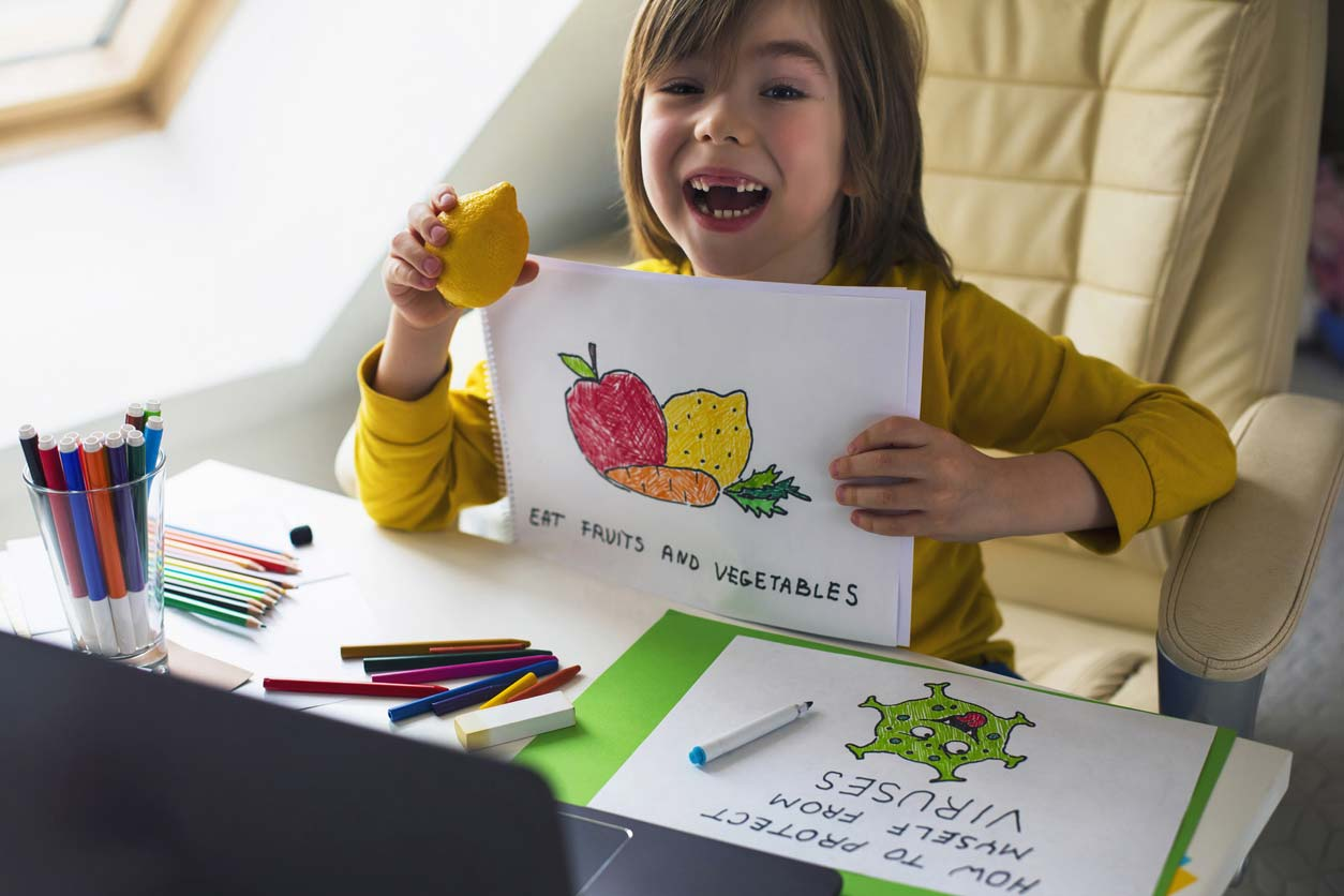 "child with drawing of what helps with covid and other viruses: ""eat fruits and vegetables."""
