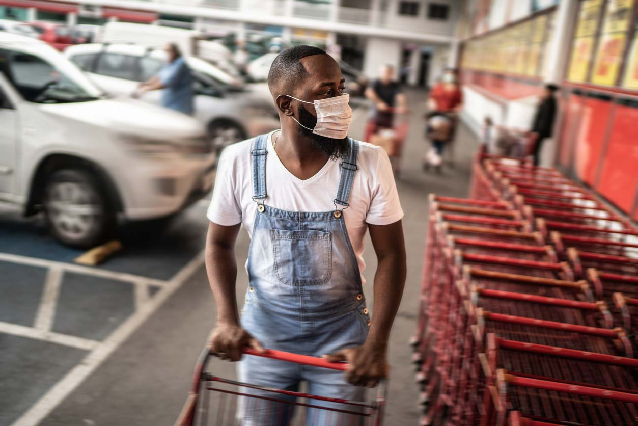 Black man with face mask grabbing grocery cart