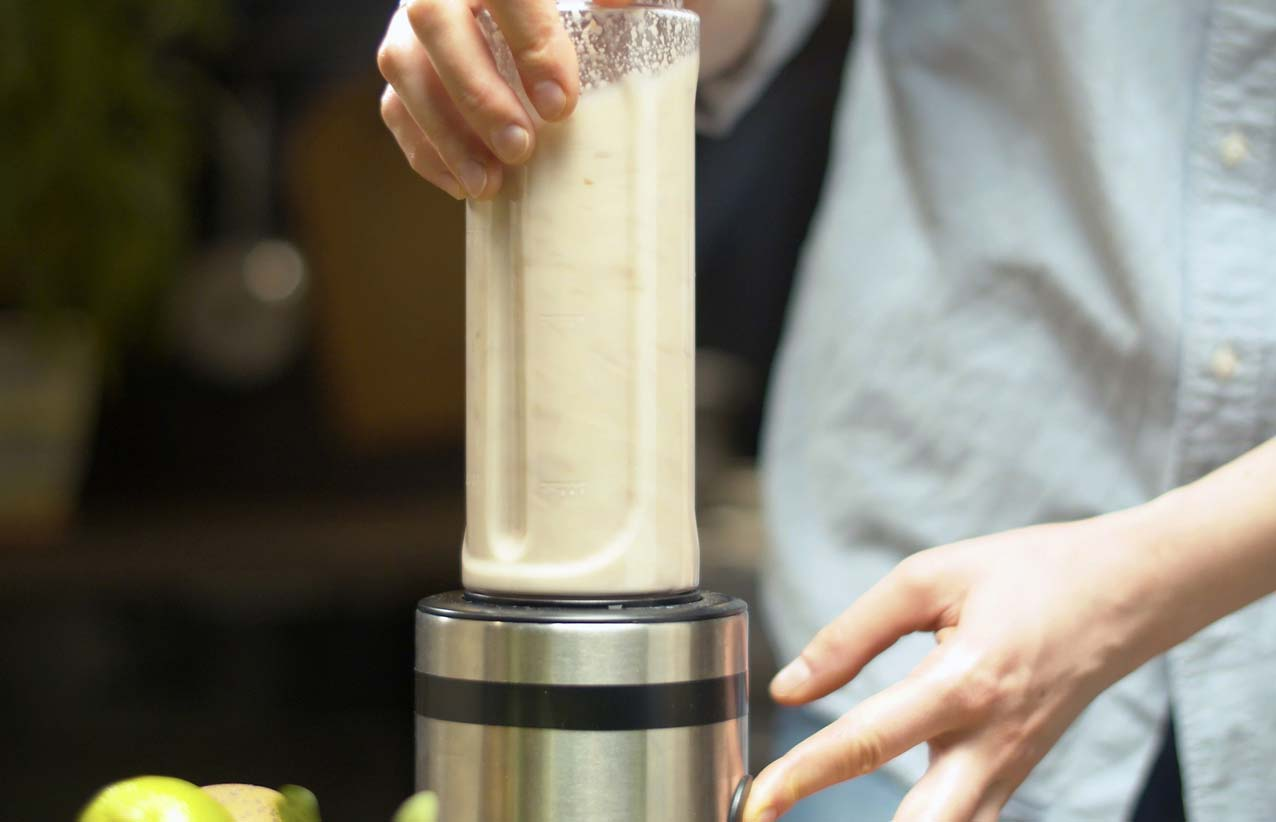 Woman making almond milk in a blender