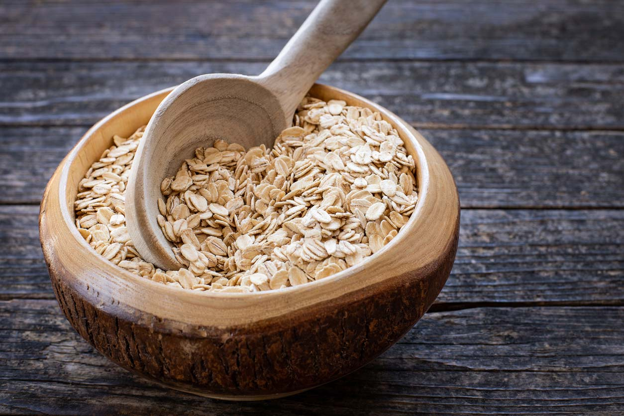 Oats in wooden bowl being scooped with wooden spoon