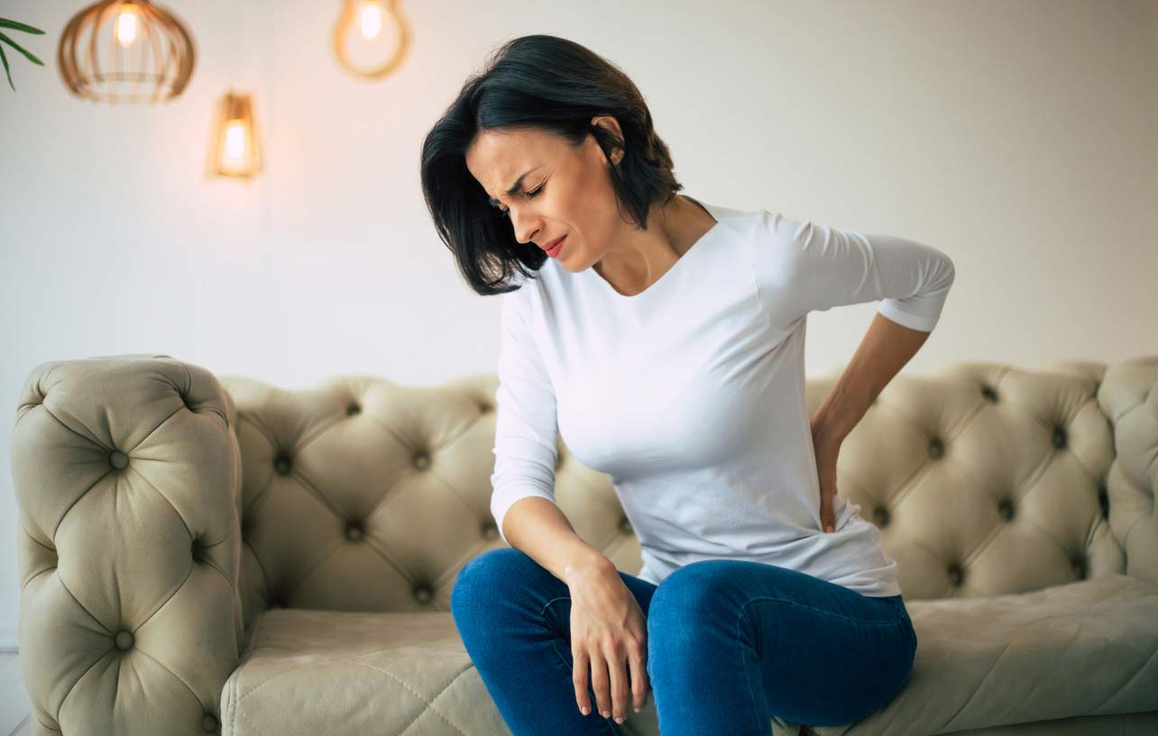 woman holding lower back while sitting on edge of couch