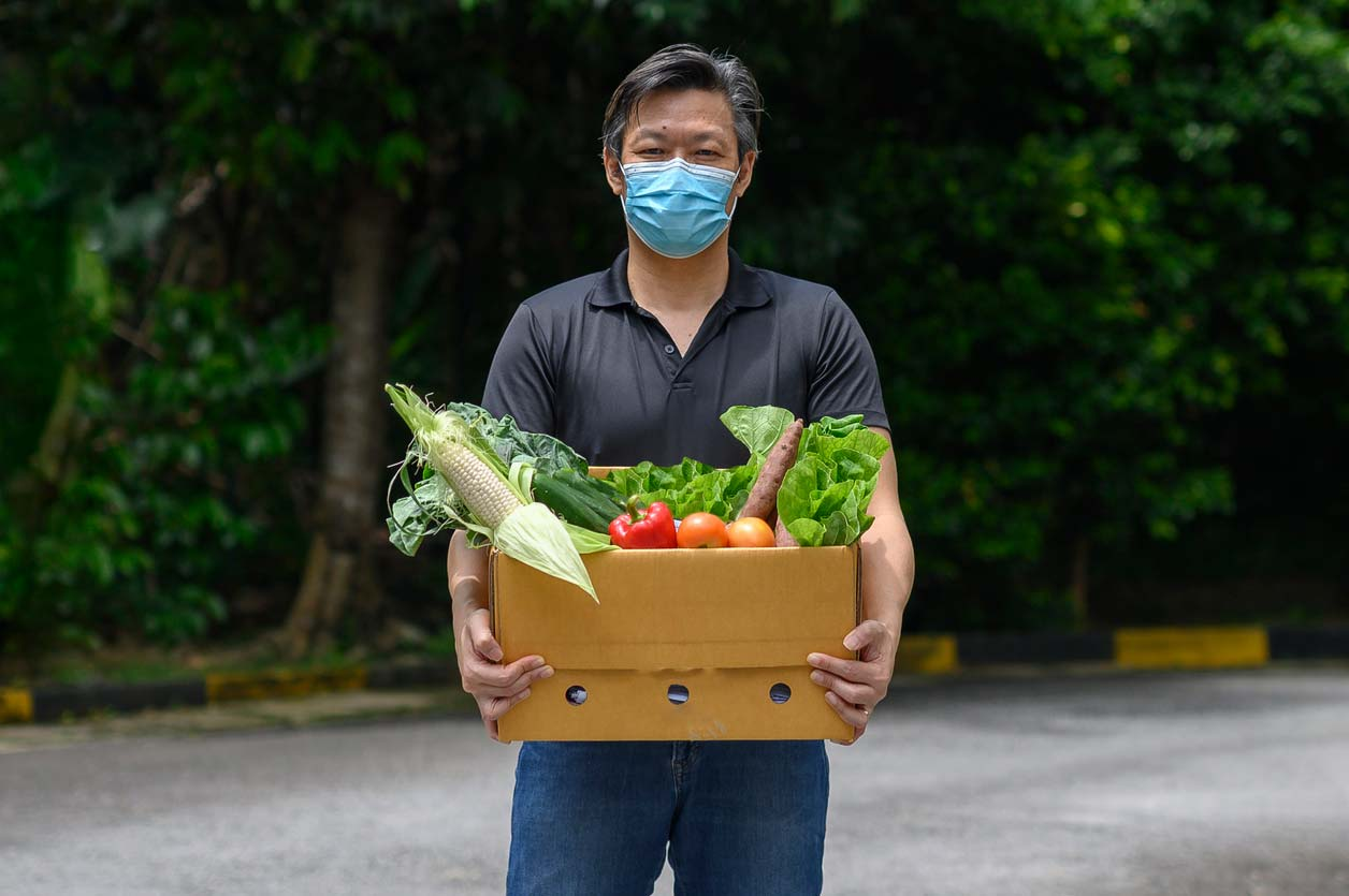 Man with face covering carrying a CSA produce box