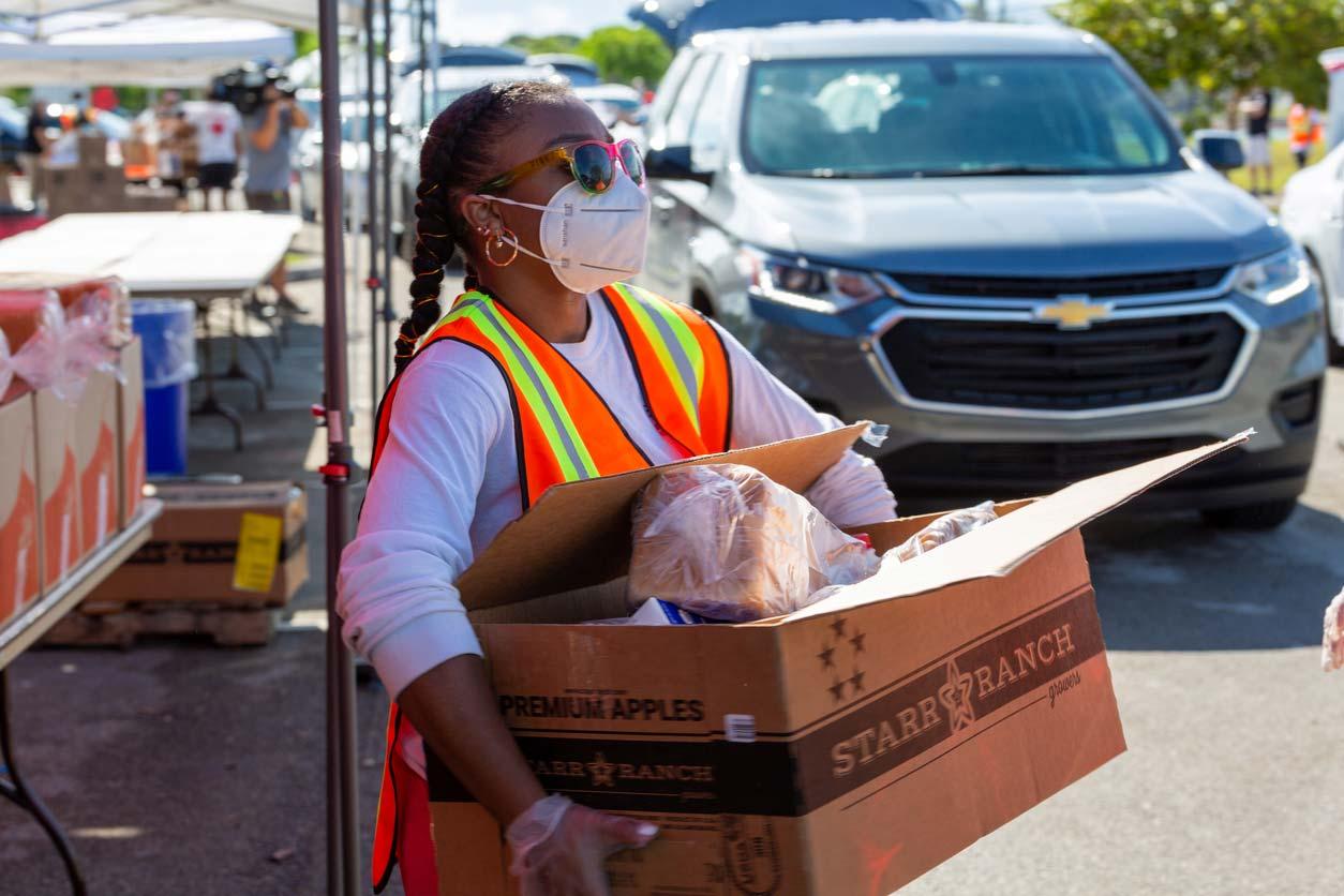 Woman volunteer carrying box of food to drive-thru food pantry