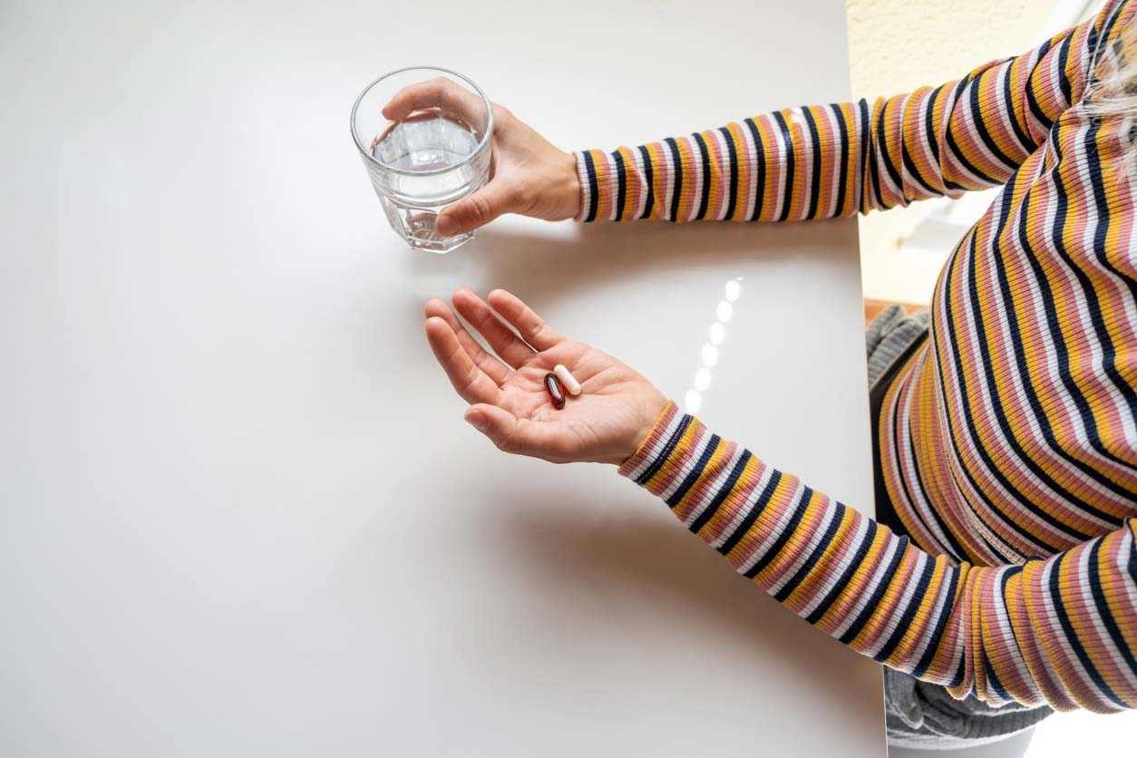 close up of supplements and water glass in hands of woman