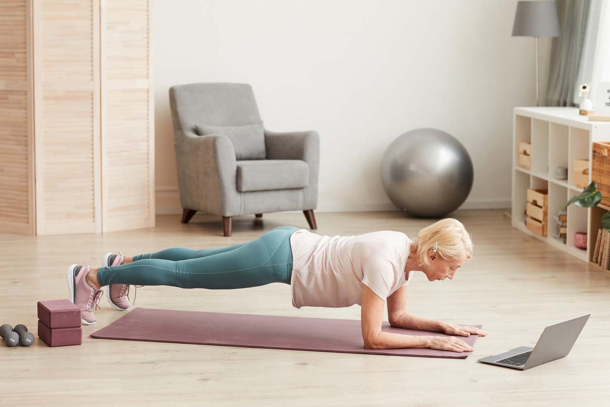 Senior woman doing weight-bearing exercise on yoga mat
