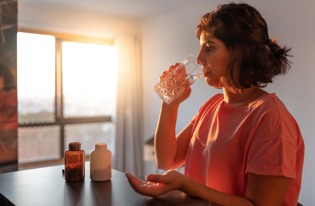 Woman taking supplements with a glass of water