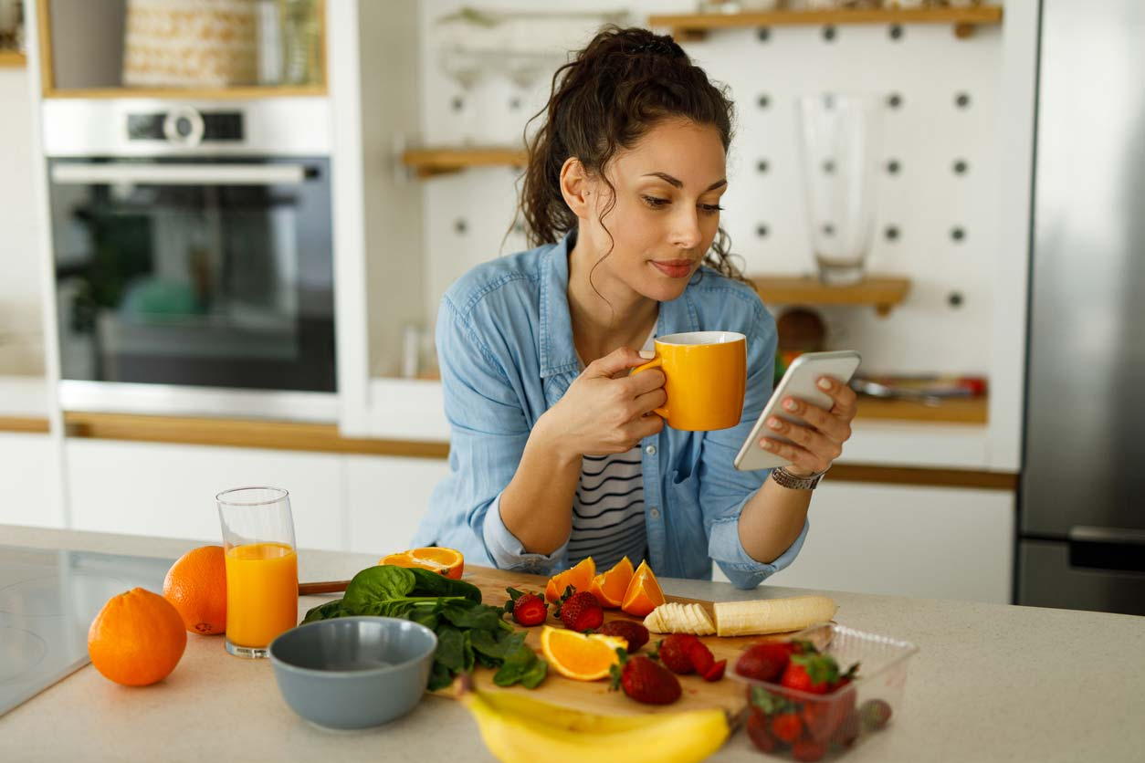 woman using phone and drinking tea while preparing greens and fruit