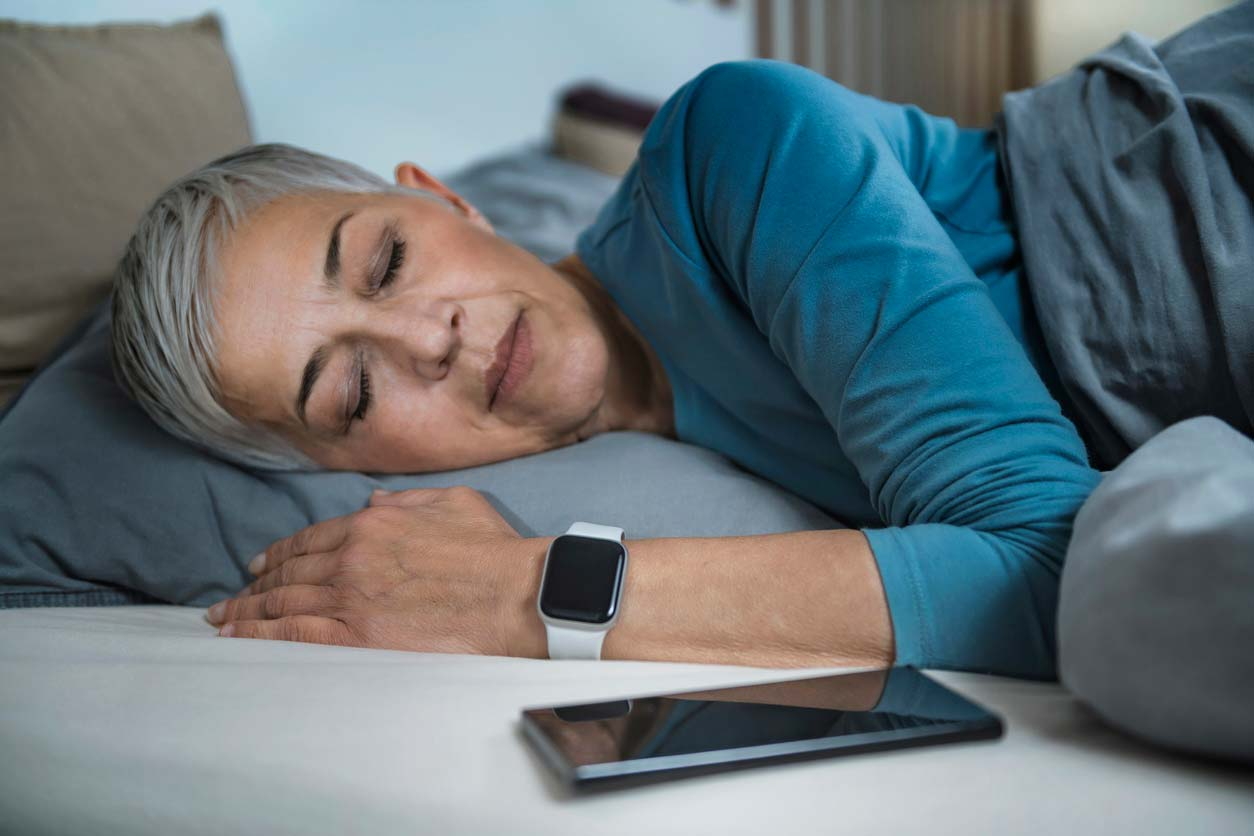 woman sleeping with health tracker on wrist and phone next to pillow