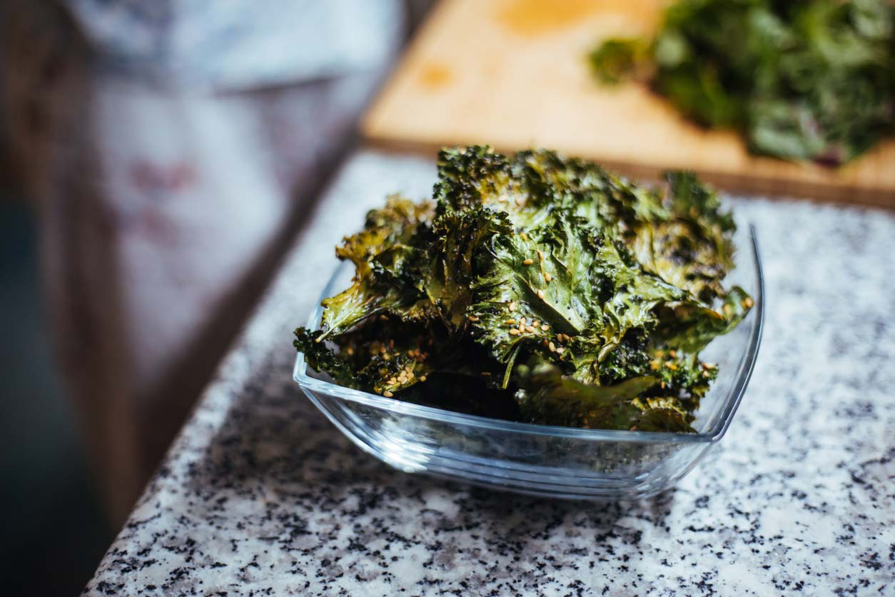 crunchy snack of kale chips in bowl on counter