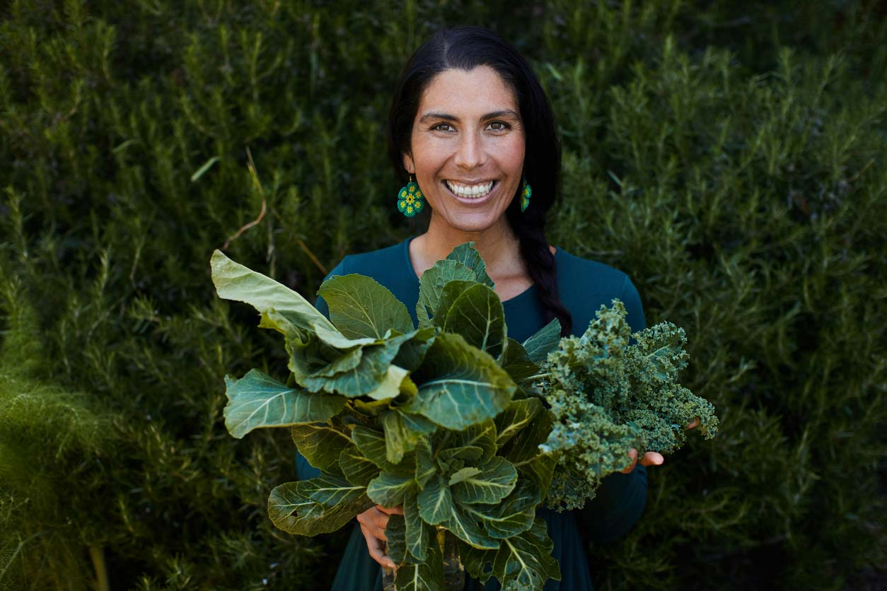 Happy woman holding fresh-picked green leafy vegetables