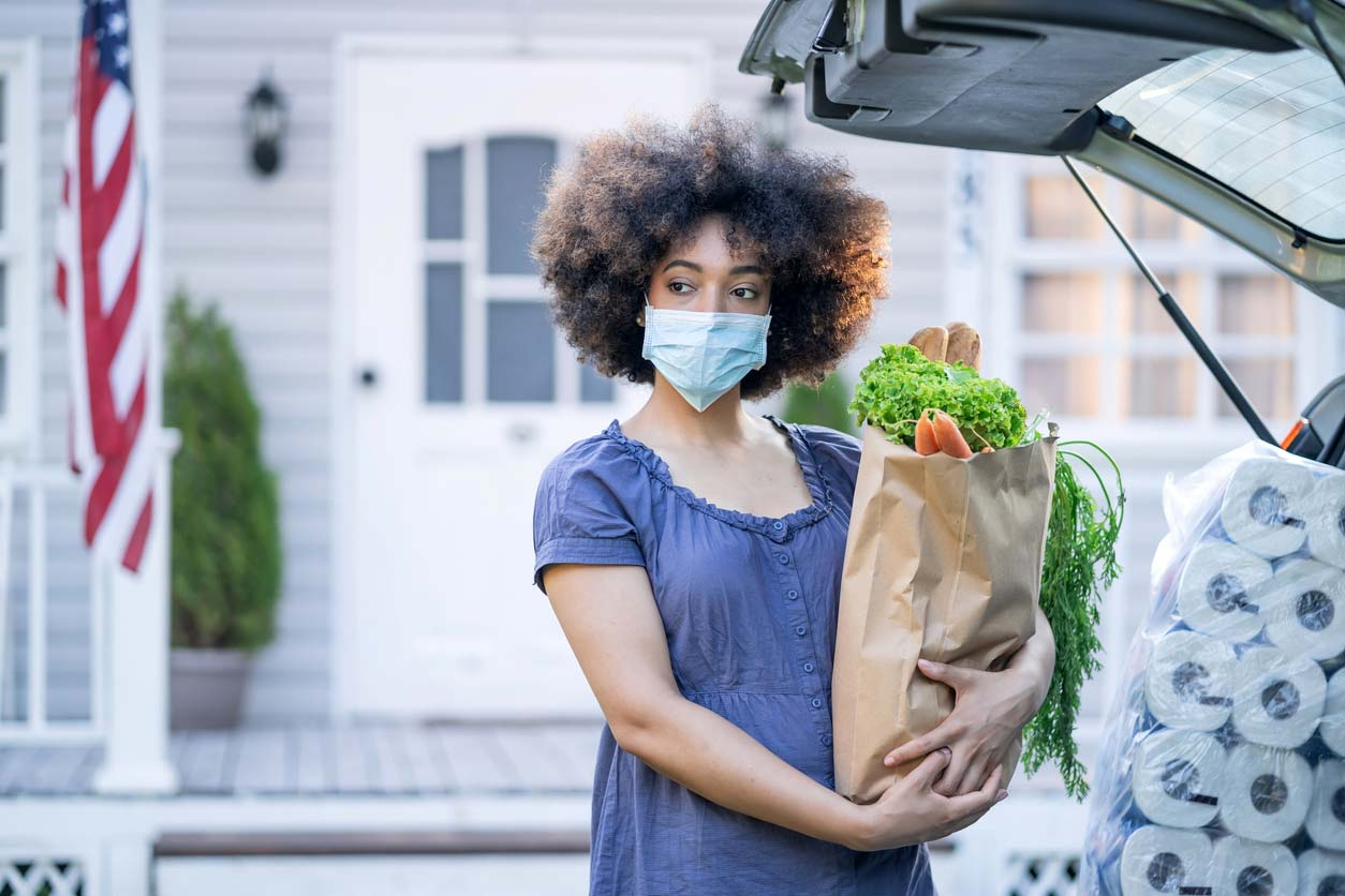 woman in mask holding groceries at back of vehicle