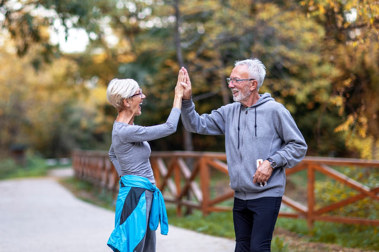 mature couple taking high five with hands after jogging in public park