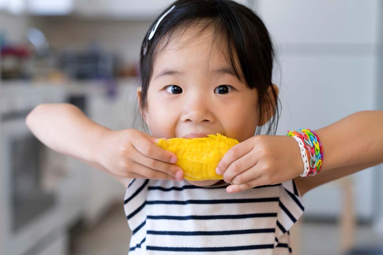 young girl eating a mango