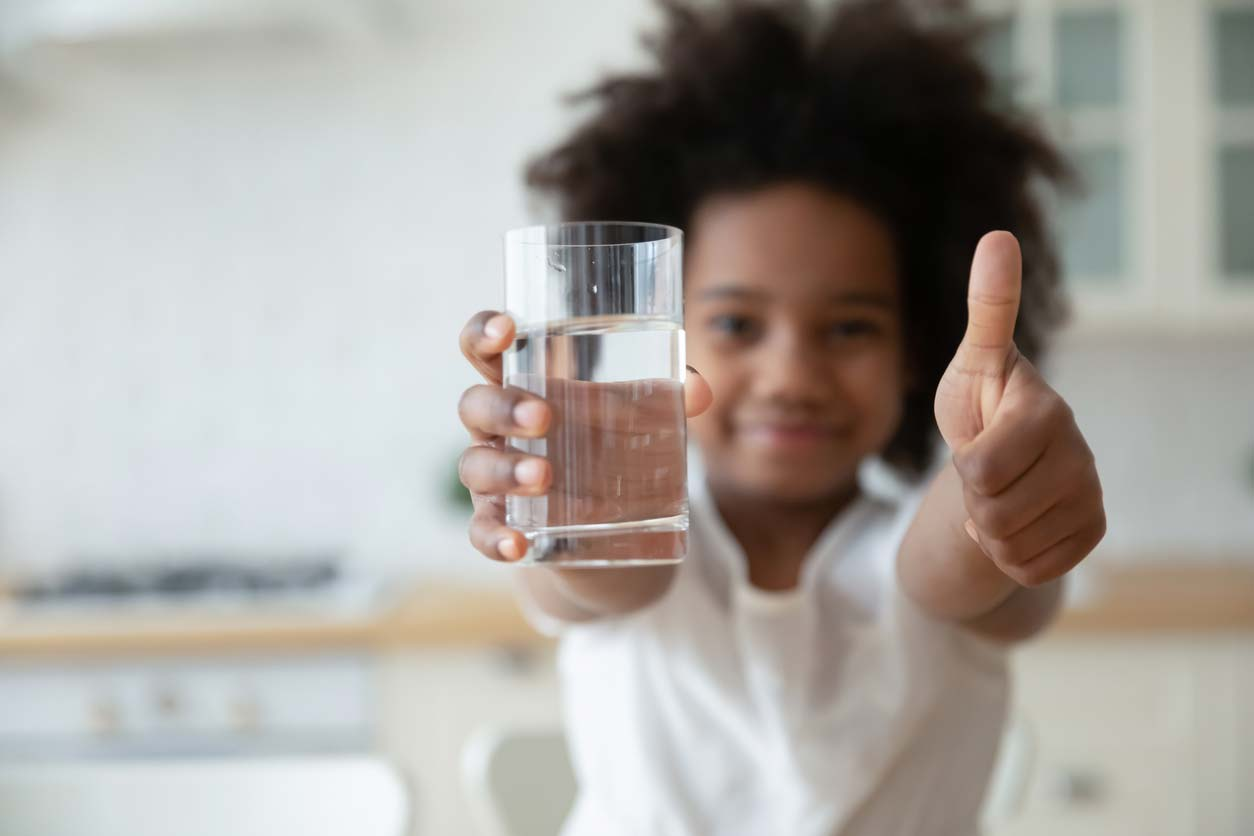 young girl holding glass of water showing thumbs up gesture