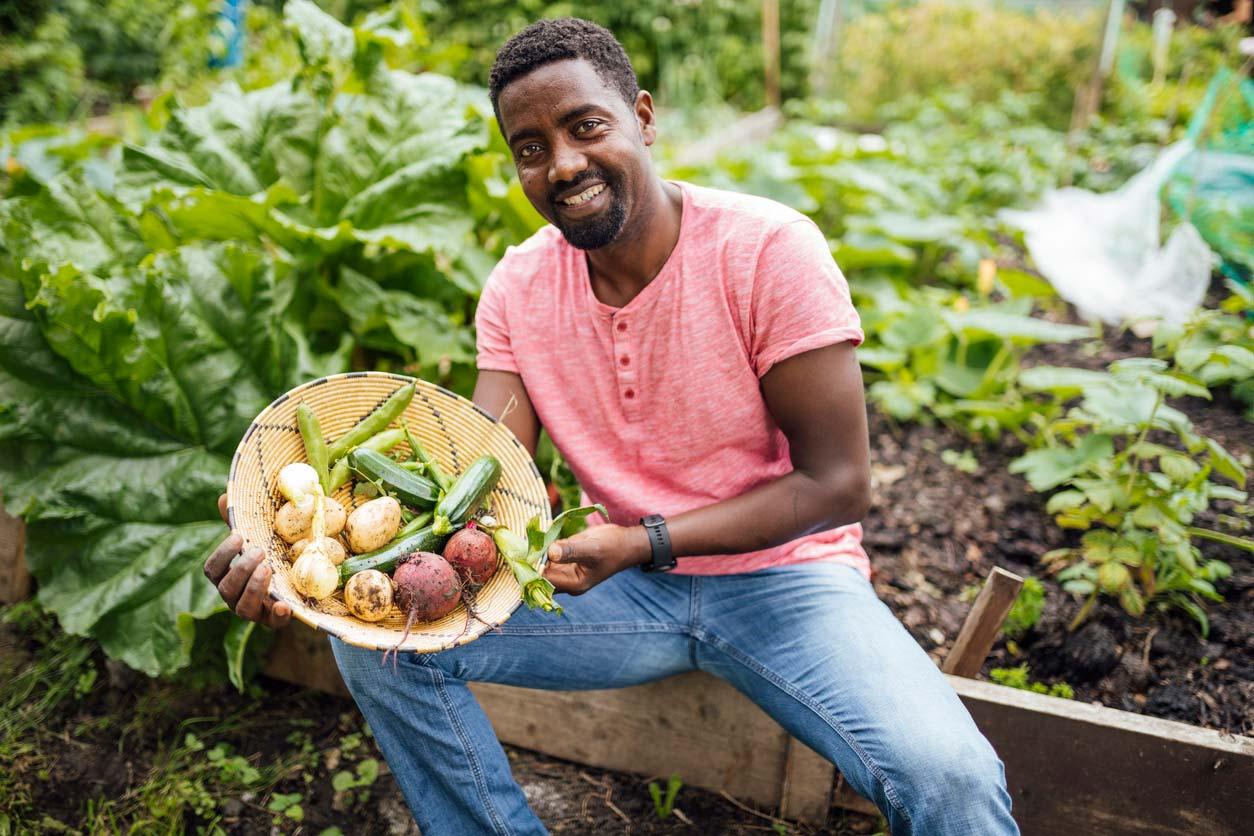 man holding basket of fresh vegetables from a community garden