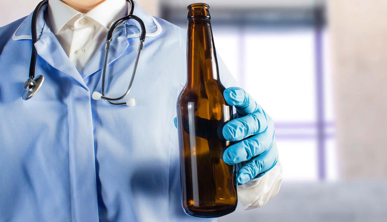 doctor in uniform holding beer bottle