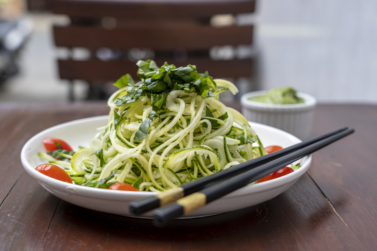 Spiralizer recipe with spiralized zucchini, cucumber, cherry tomato, garlic in a creamy pesto from avocado.