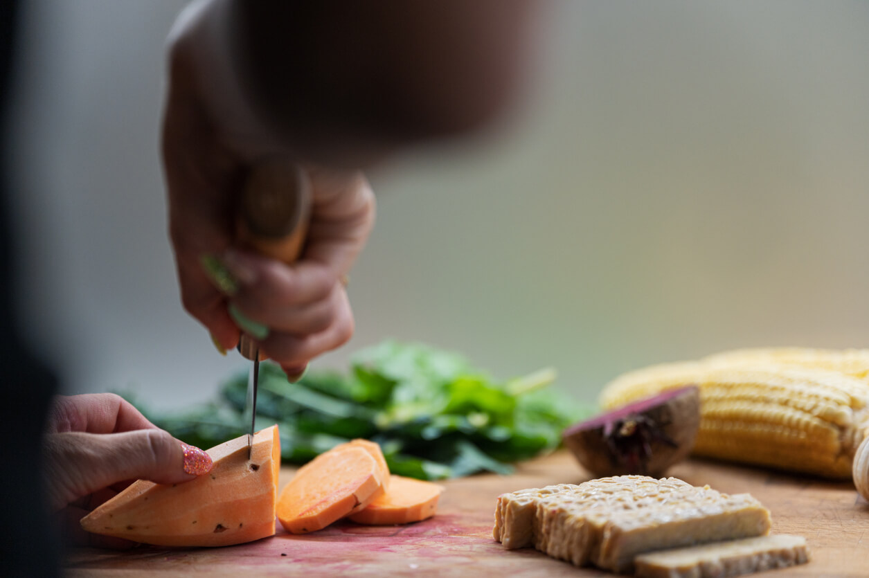 low angle view of a woman cutting tempeh on a cutting board