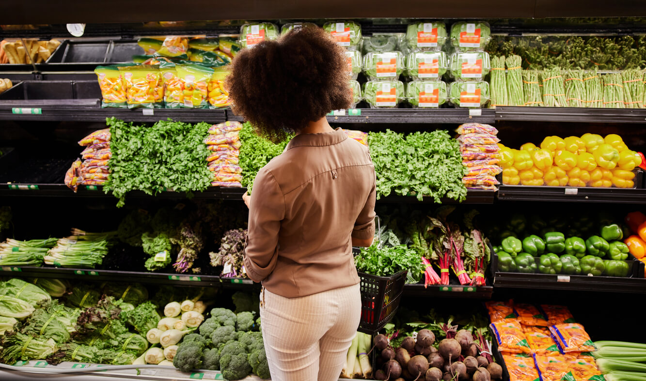 young woman looking at the produce section in a supermarket