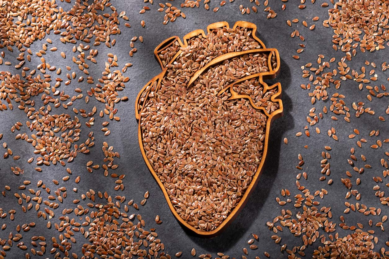 flaxseed all over a table and in an anatomical heart-shaped dish