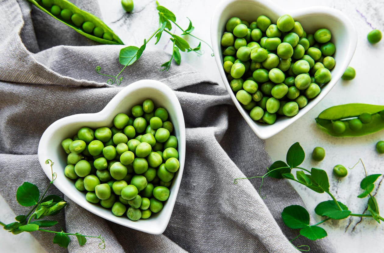 two heart shaped white bowl of green peas