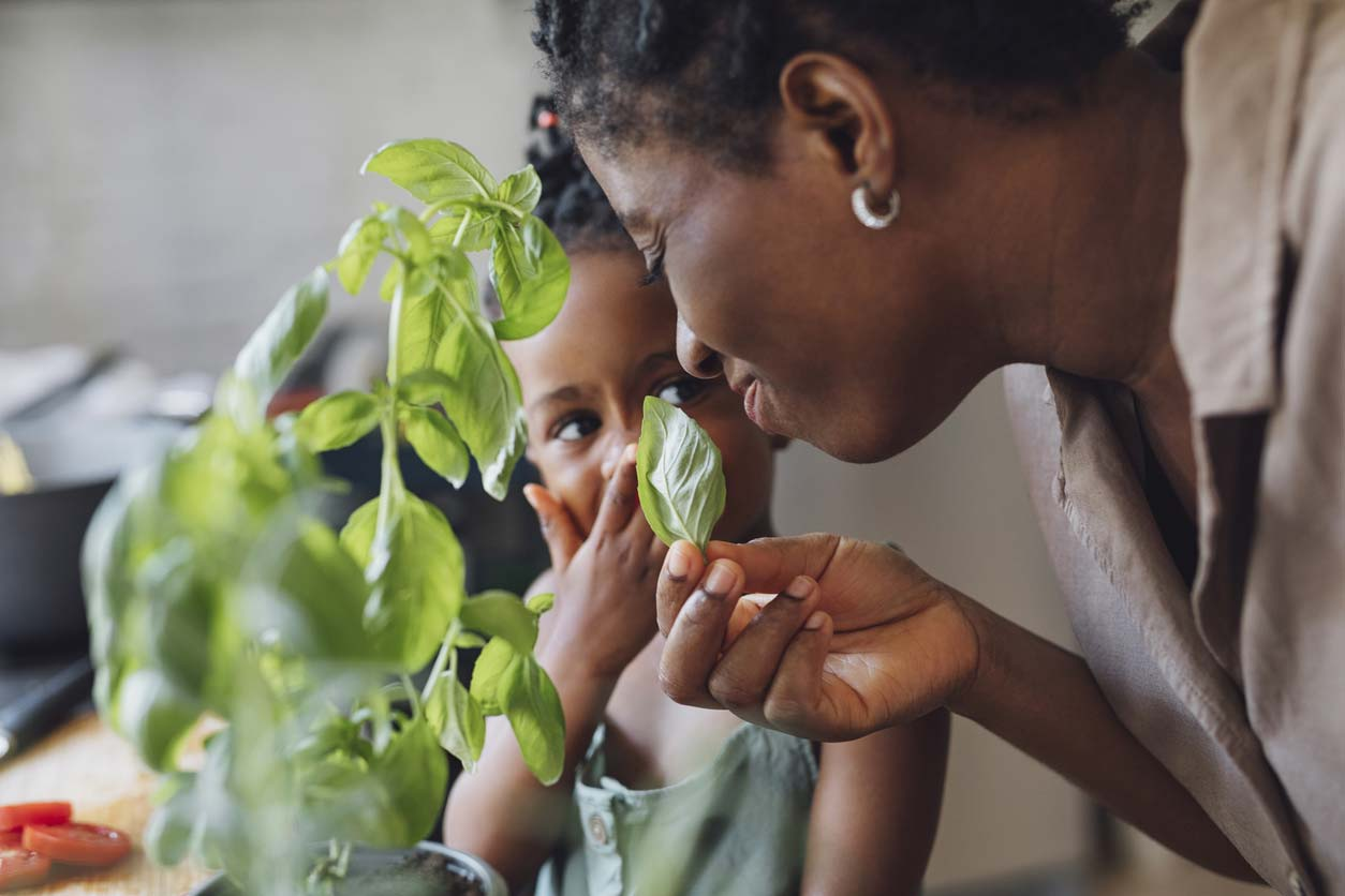 mother and daughter smelling basil
