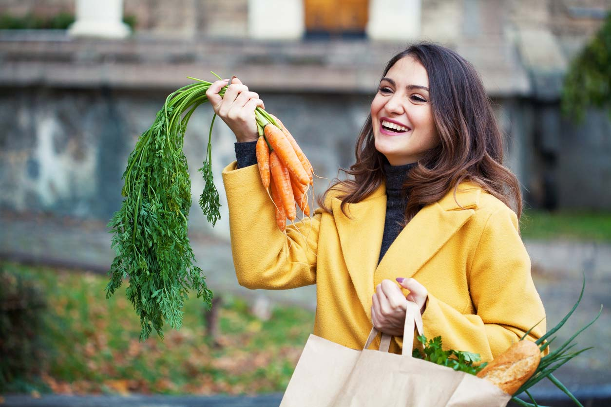 woman holding grocery bag and carrots