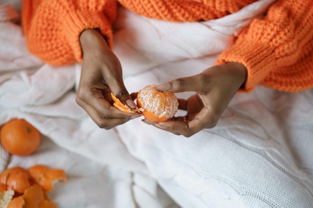 afro woman hands peeling ripe sweet tangerine wear orange sweater lying in bed under