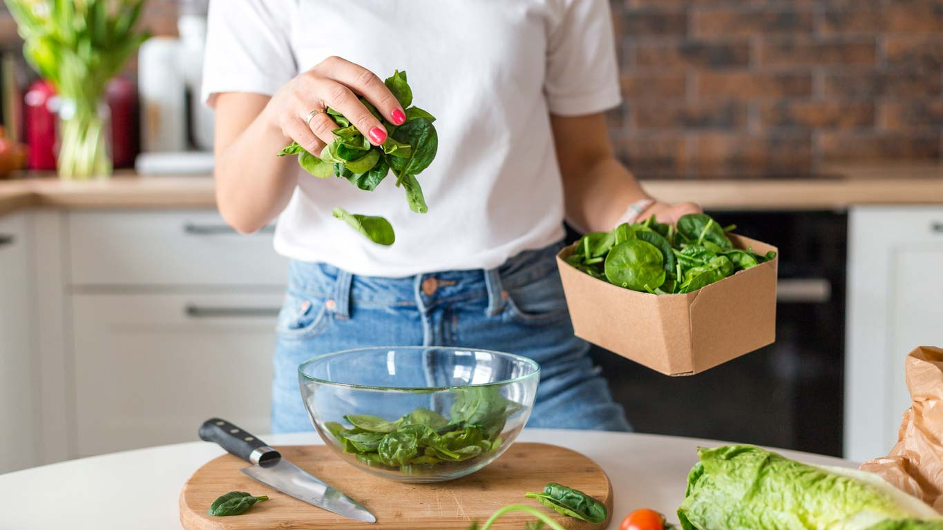close up of woman in white shirt prepping spinach salad