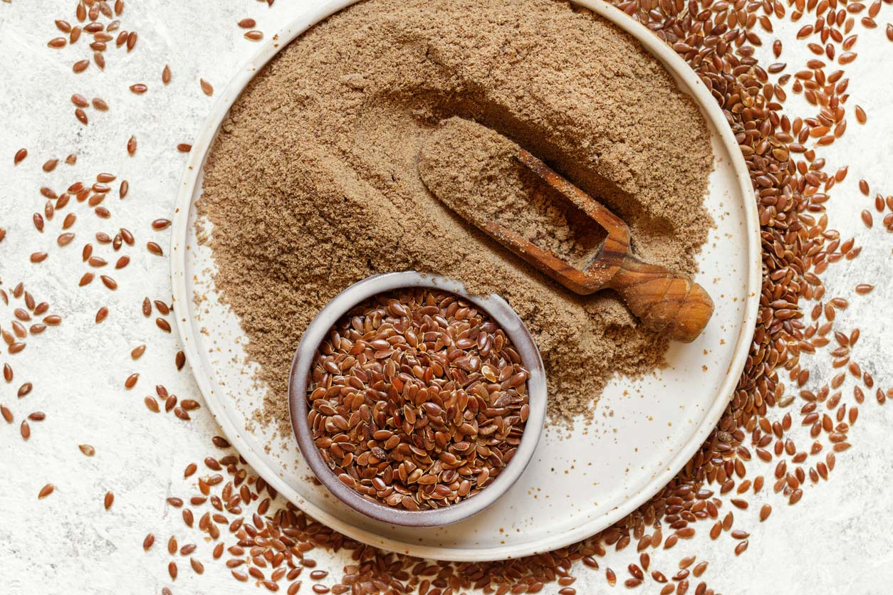 raw flaxseeds in bowl on plate with flax flour
