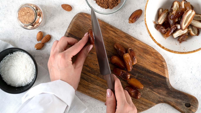hands cutting dates on cutting board