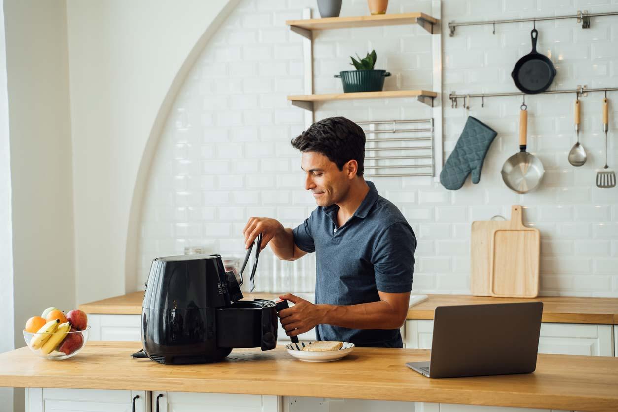 man using air fryer in kitchen