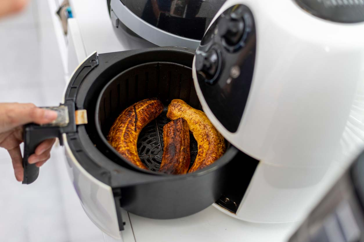 opening air fryer with cooked bananas