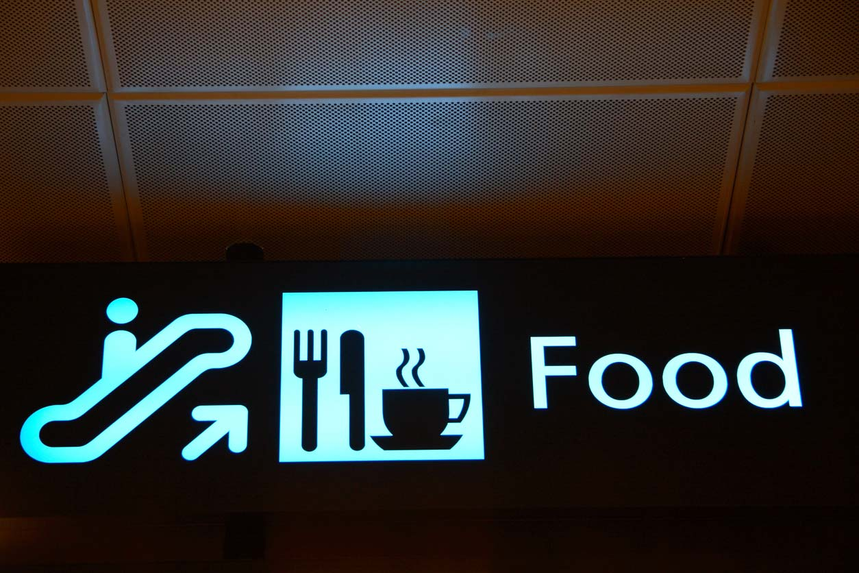 illuminated sign with pictograms of escalator and food