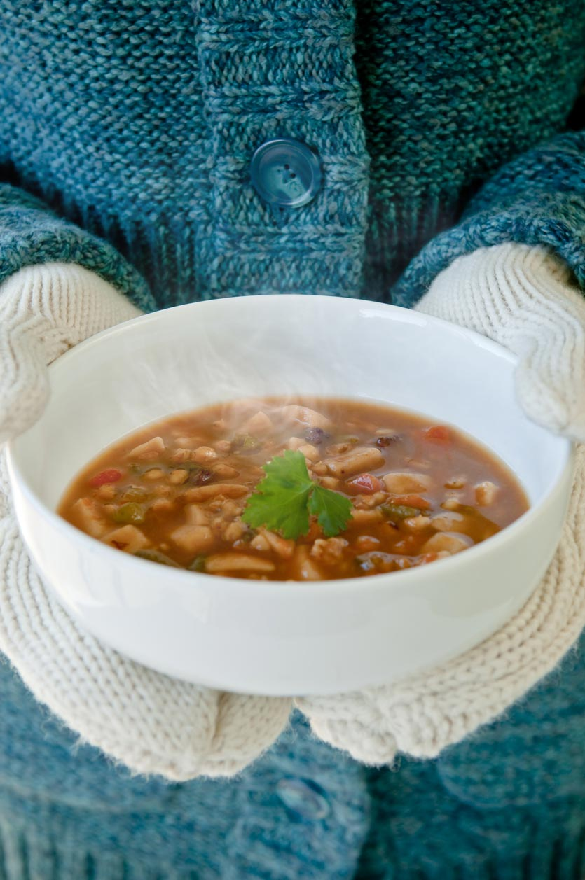 bowl of soup in mittened hands