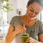 A woman stirring a green smoothie with a straw in her kitchen