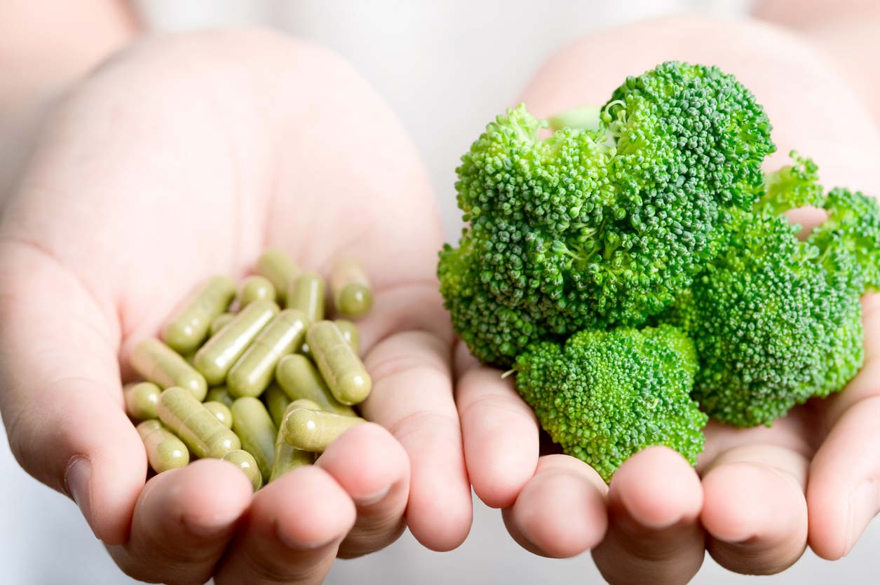 Hands holding broccoli sprouts supplements with sulforaphane and a crown of broccoli
