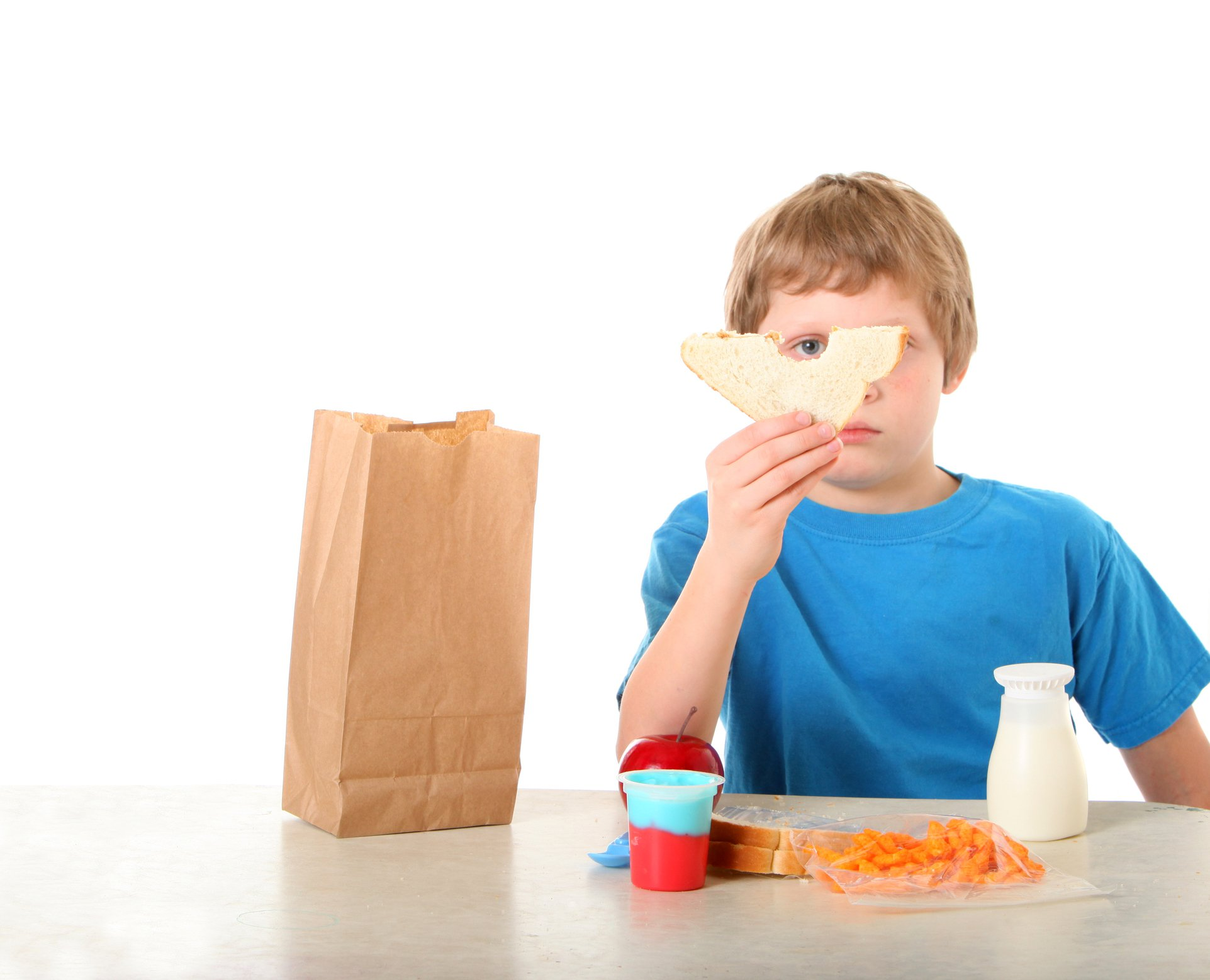 Boy at table eating an unhealthy packed school lunch