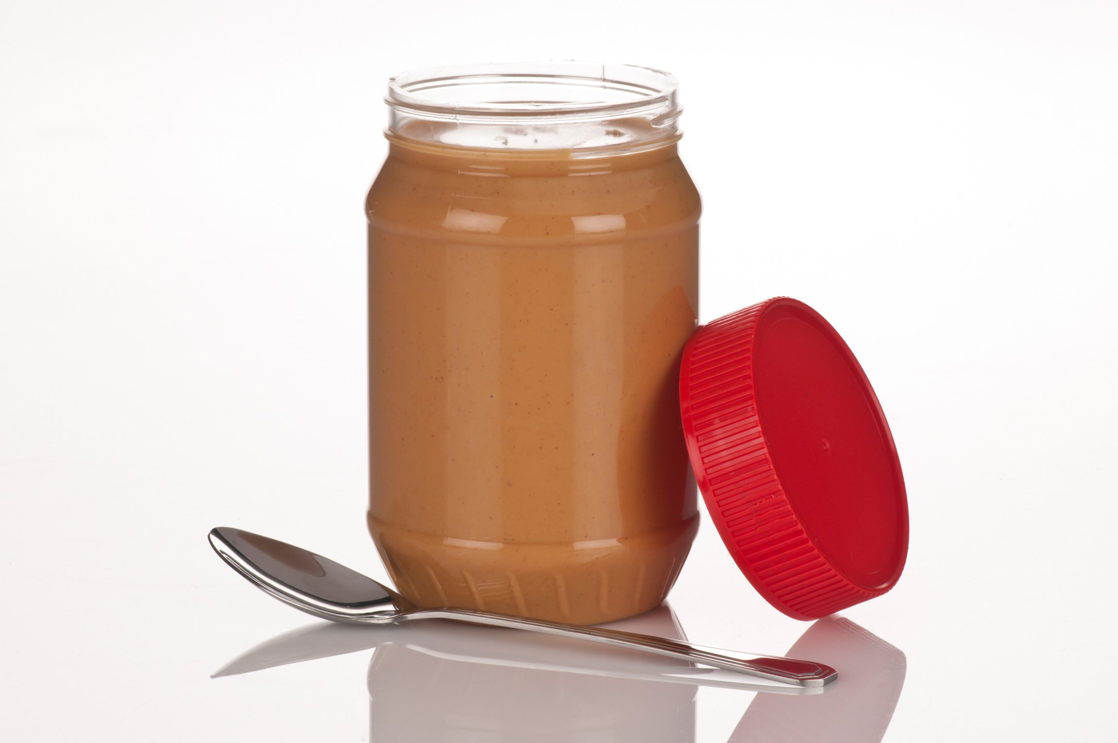 A jar of peanut butter with a spoon and the lid off