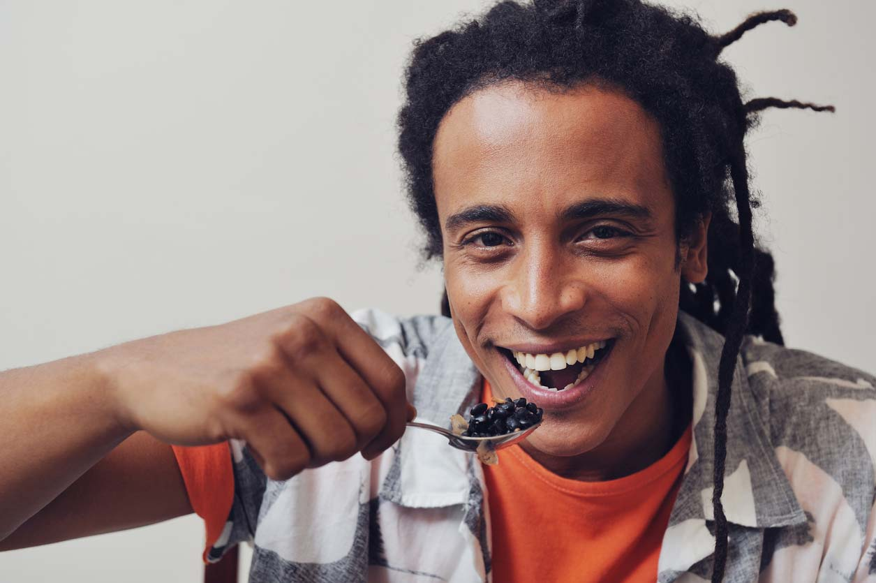 man happily eating spoonful of black beans