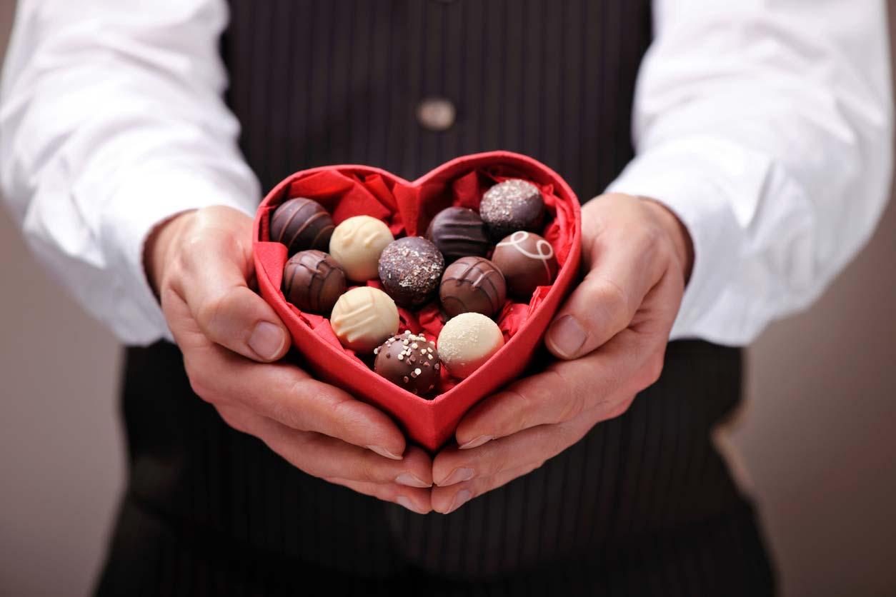 man holding heart shaped box of chocolates