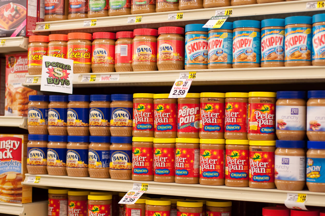 a variety of peanut butter and other nut butter on shelves in grocery store