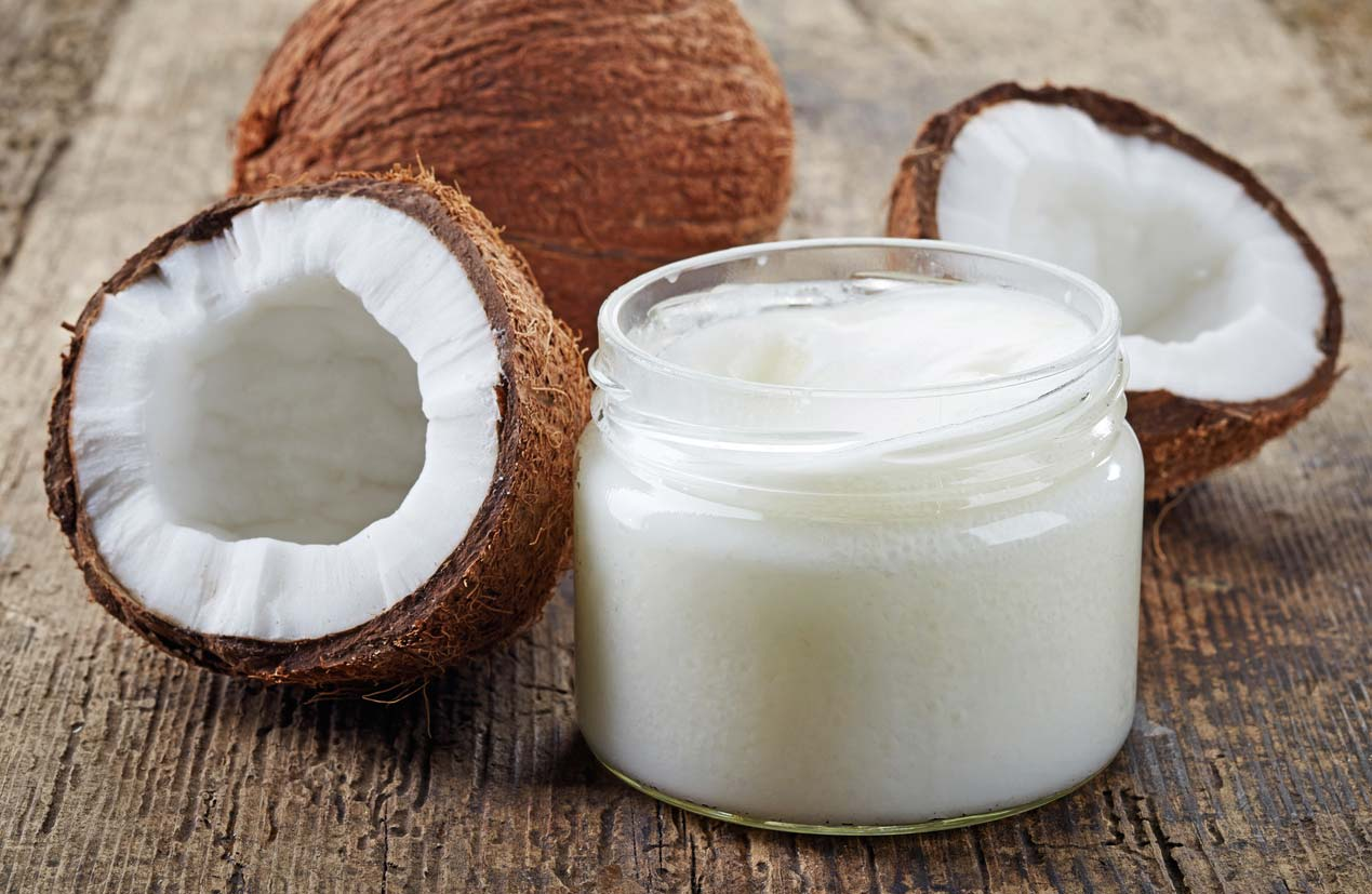Fresh coconuts and jar of coconut oil, which is often a vegan substitution in baking