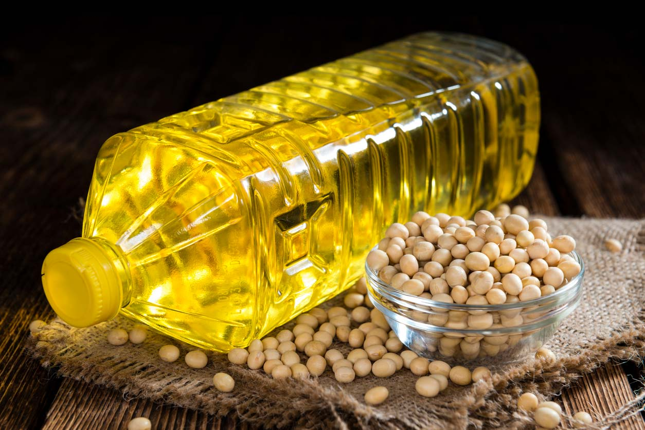 bottle of soybean oil next to soybeans