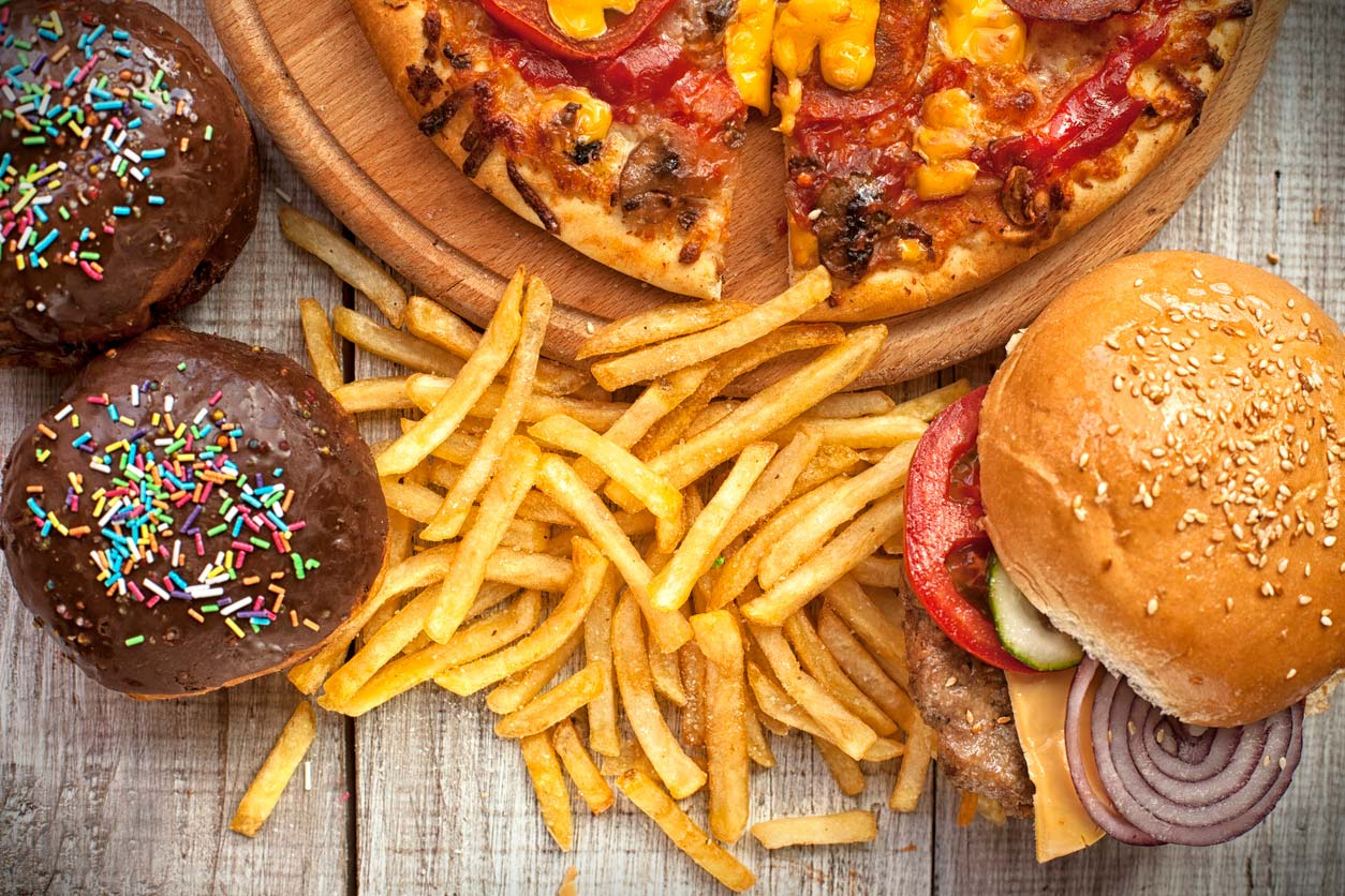 Pizza, burger, fries, and cupcakes on table: Unhealthy foods for weight gain